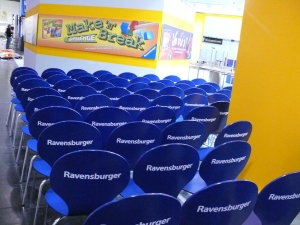 Row after row of blue chairs with 'Ravensburger' on the back in white lettering